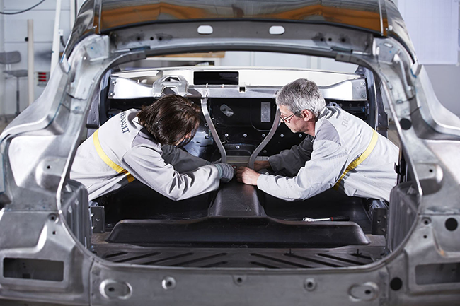 Two automotive engineers inspect the inside of a Renault vehicle car frame