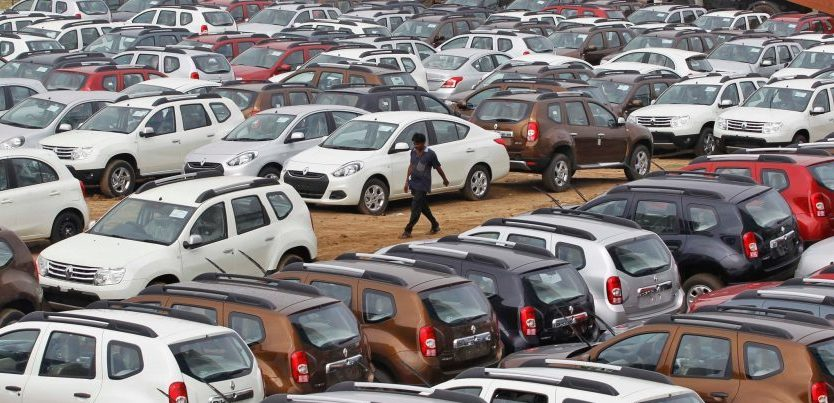 A man walks through a full parking lot of Renault cars in Ahmedabad, Gujarat, India.