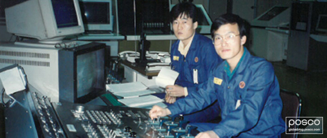 Kim Yong-Hoon working and a fellow employee working at an operation board at the No. 2 Hot Rolling Mill in 1993