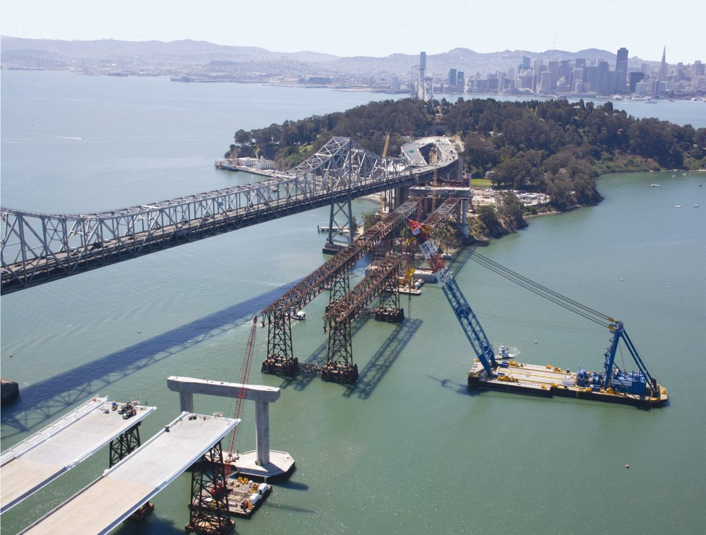 A floating crane for lifts prefabricated deck sections onto the San Francisco-Oakland Bay Bridge during construction in 2009
