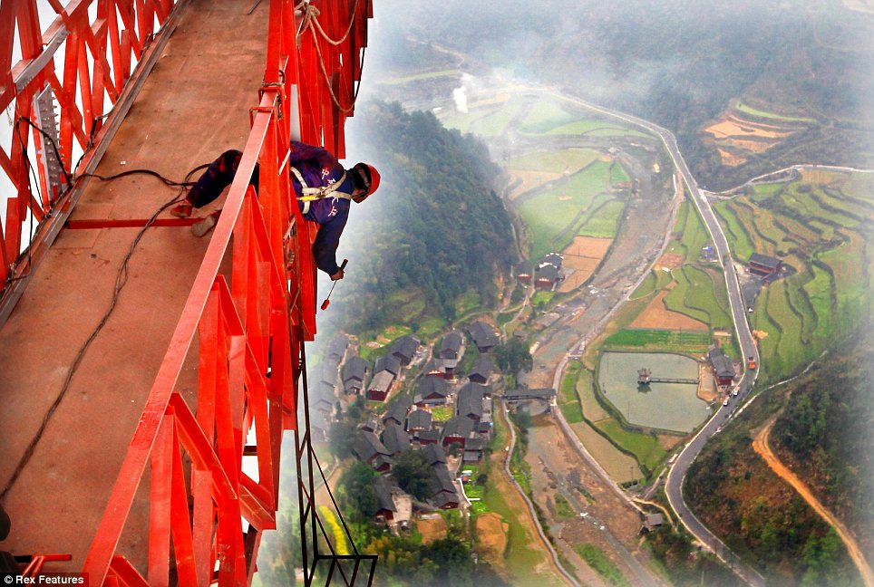A worker paints the Anzhaite Long-span Suspension Bridge in Jishou, Hunan, China