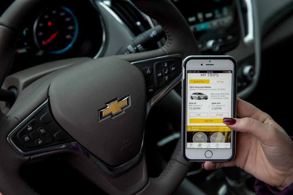 A person inside a GM vehicle is showing Maven, a new car sharing service, on her smartphone screen.
