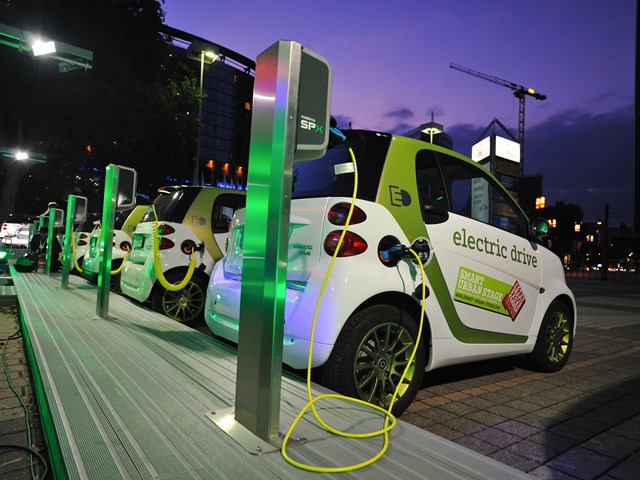 Electric vehicles charging at a charging station.