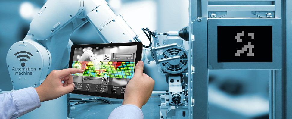 A worker in a smart factory controlling robots with a smart tablet.