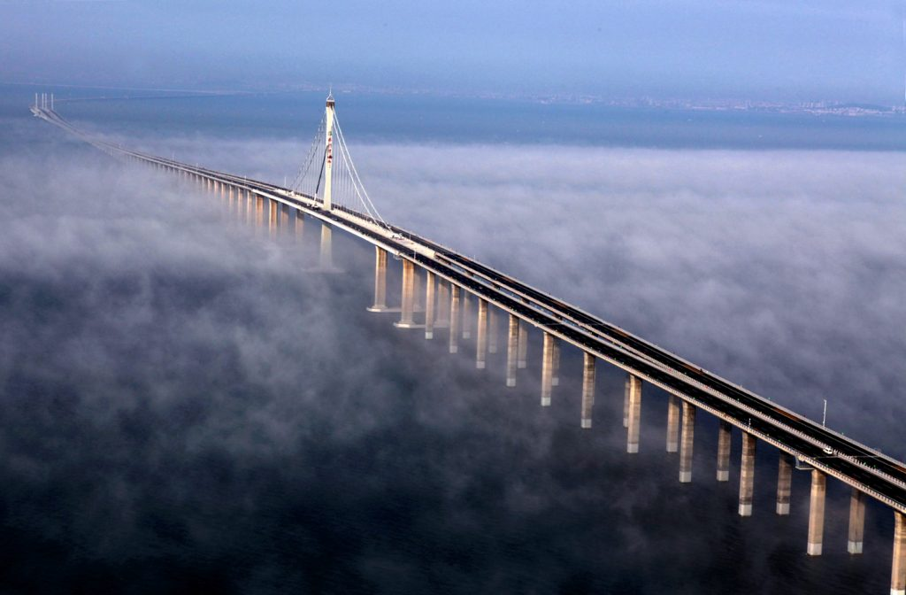 Bird's eye view of Jiaozhou Bay Bridge in China covered by clouds.