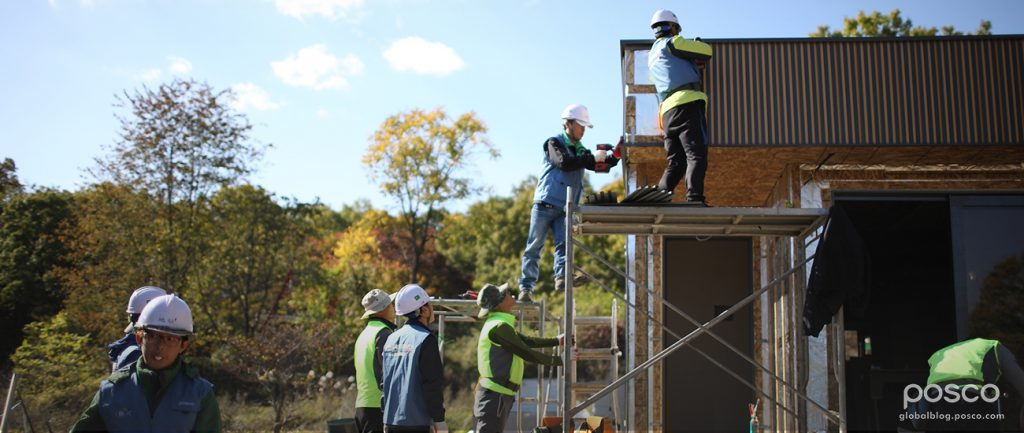 POSCO employees construct a steel house.