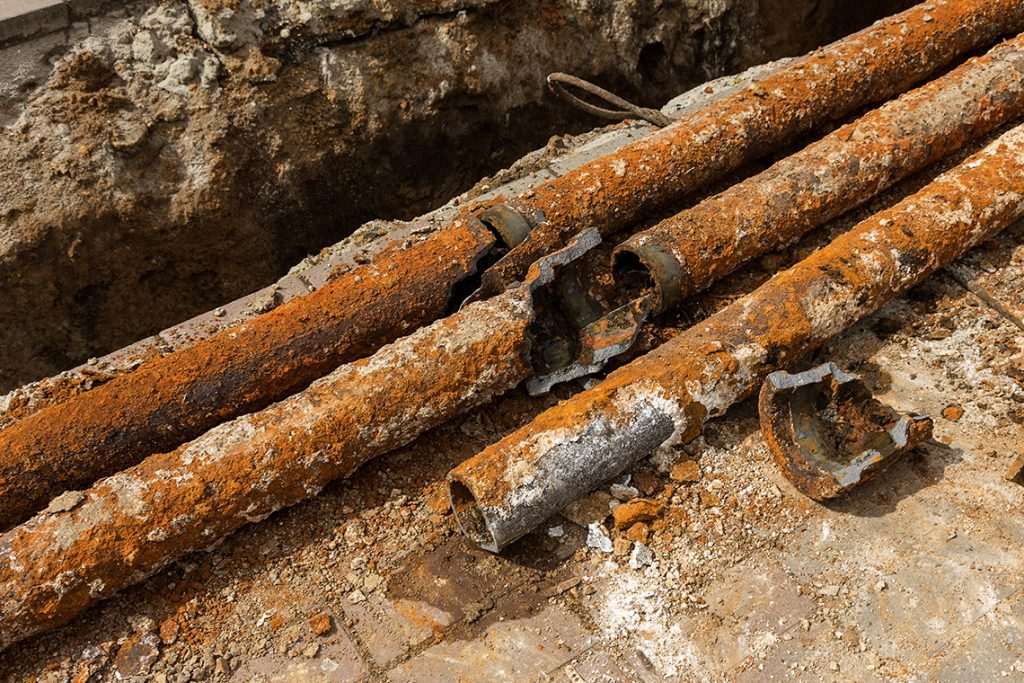 Three broken and rusty water pipes.