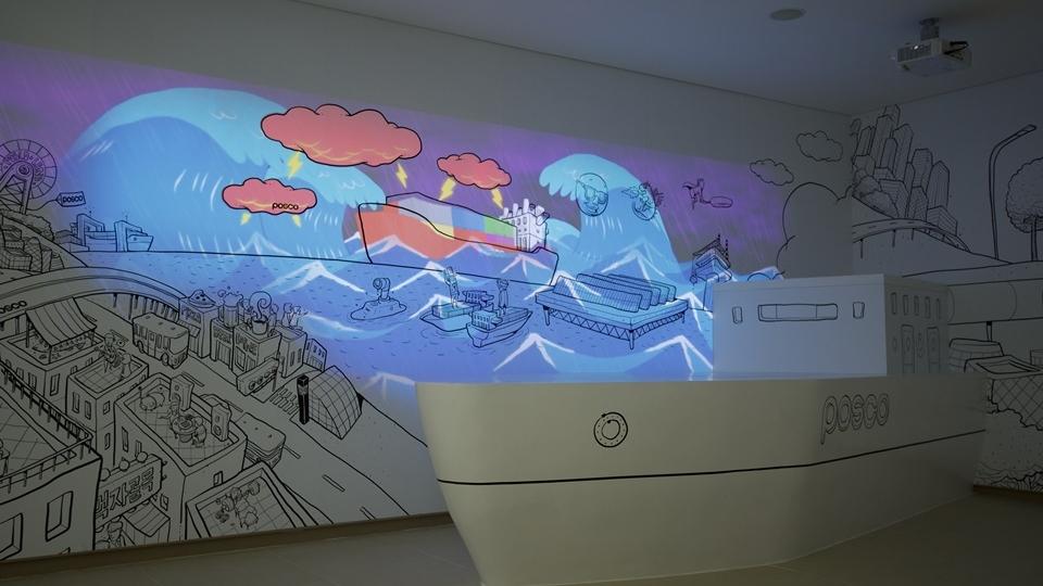 """키네틱과 미디어아트 활용, 제품종합전시관 """"Steel Gallery"""" 사진 입체적인 배모형이 있으며 벽에는 천둥 전개 그리고 파도가 일렁이고 있다. 빨간색 파란색으로 칠해져있다."""