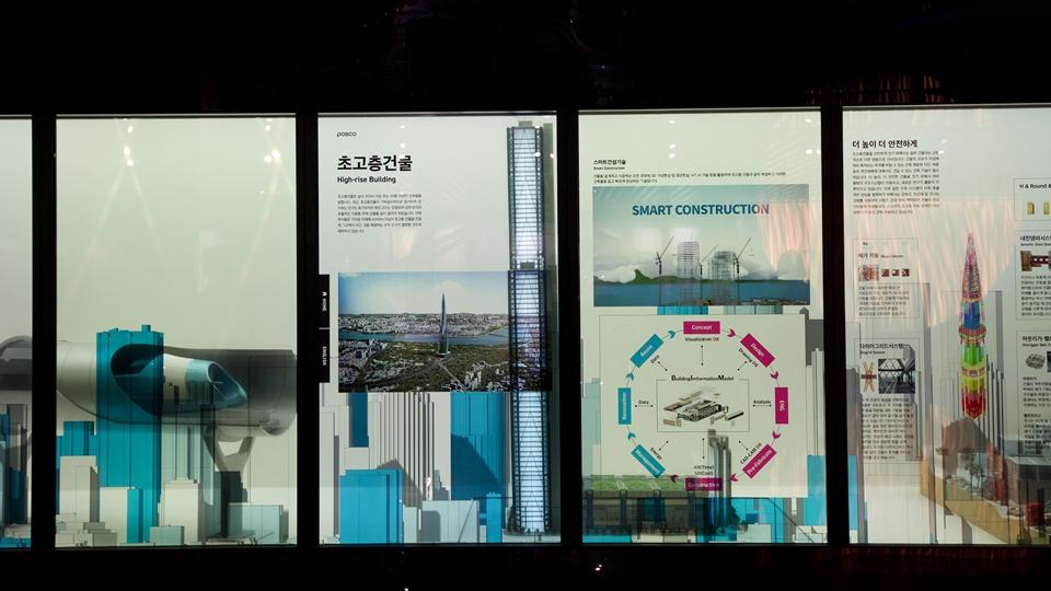 """키네틱과 미디어아트 활용, 제품종합전시관 """"Steel Gallery"""" 사진 초고층건물 high-rise building 스마트 건설기술의 선명 smart construction 더높이 더 안전하게라고 적혀있으며 여러가지 이야기가 적혀있다."""