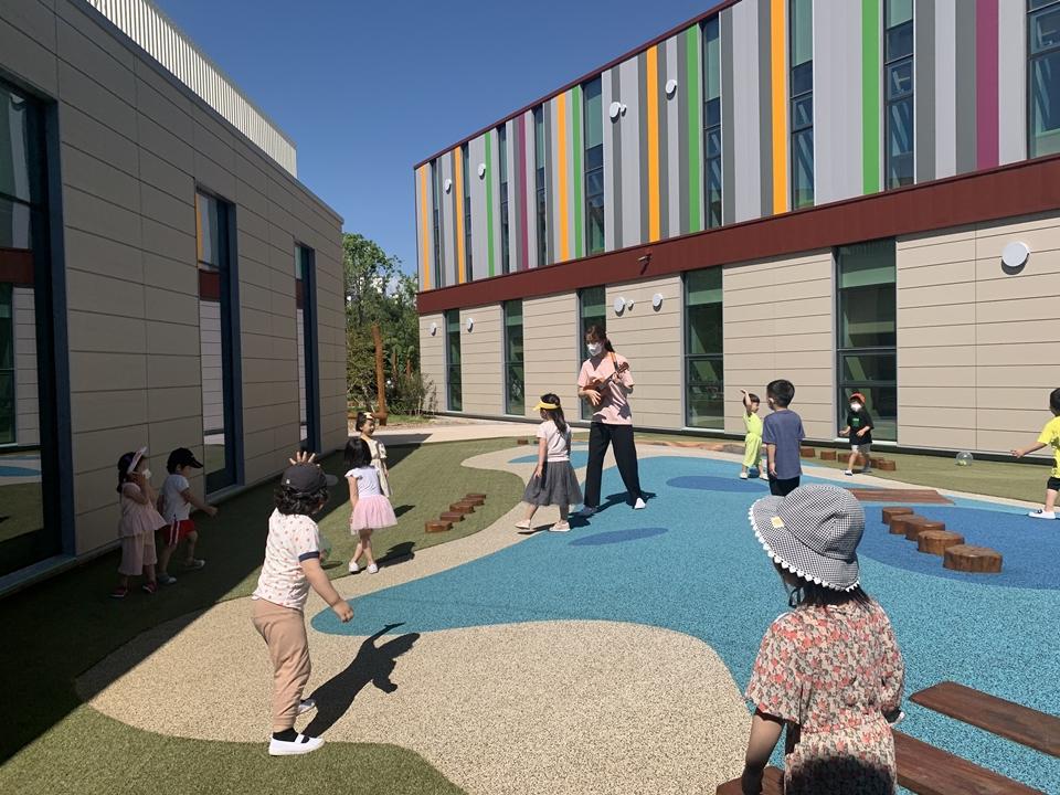 포스코 금당어린이집의 원아들이 외부 놀이 공간에서 선생님의 기타 연주에 맞춰 신나게 뛰어놀고 있는 모습