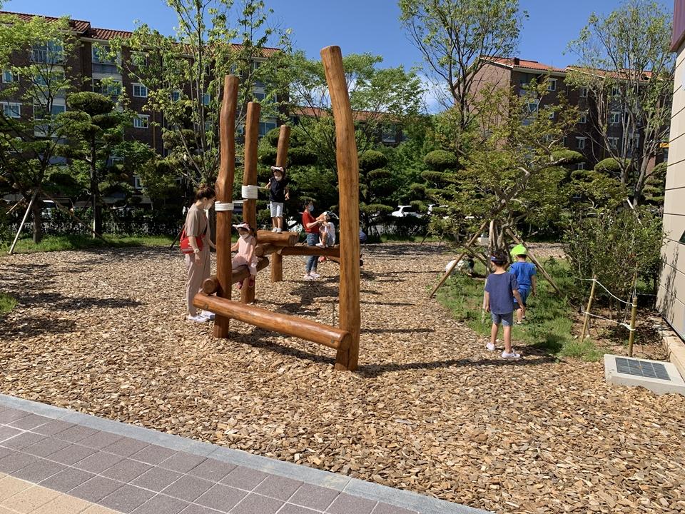 포스코 금당어린이집의 숲속 놀이터에서 원아들이 학부형등과 징검다리를 건너며 신나게 놀고 있는 모습.