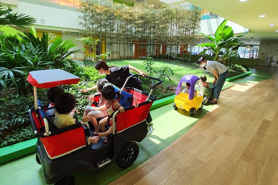 포스코 동촌어린이집 2층 높이의 실내 정원에서 원아들이 자연을 직접 체험하고 있다. 학부형과 아이들이 장난감 자동차를 타고 다니며 정원을 감상하는 모습