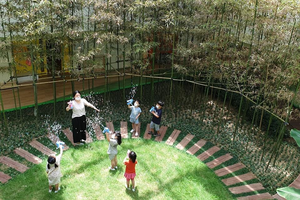 포스코 동촌어린이집 2층 높이의 실내 정원에서 원아들이 자연을 직접 체험하고 있다. 선생님과 비누방울 놀이하는 모습