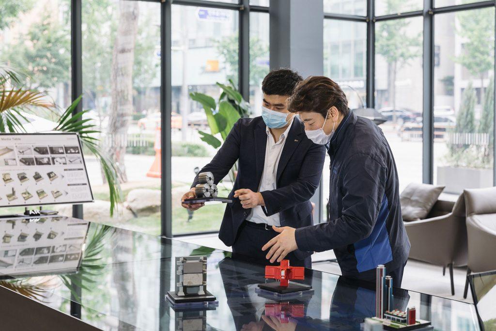 포스코의 최득용 대리가 더샵 갤러리 1층에 있는 미디어 테이블에서 4가지 종류의 강건재 제품 모형을 들고 설명하고 있다