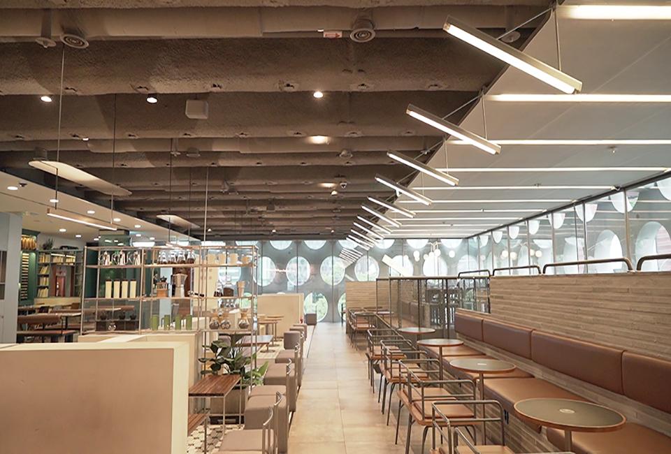 천장에 별도의 마감재를 덮지 않아 내화뿜칠이 된 TSC합성보를 그대로 볼 수 있는 어반하이브 내부 카페의 모습.