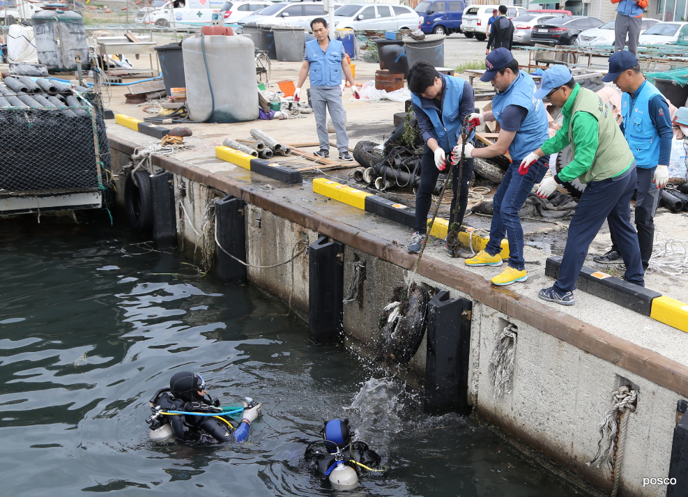 잠수복을 입은 두 사람이 바다에서 지상으로 봉사단에게 전달하는 모습. 항구에서 폐타이어를 수거해 지상 봉사자에게 전달하는 포스코 클린오션봉사단