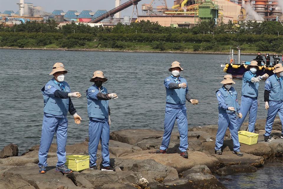 포스코 최정우 회장(사진 왼쪽에서 첫 번째)이 1일 포항 형산강에서 포스코노동조합 18대 집행부와 함께 수질정화를 위해 친환경 미생물로 만든 EM 흙공을 던지고 있다