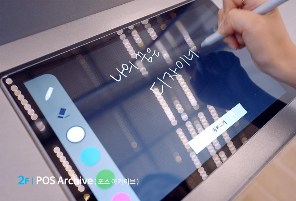 2F POS Archive(포스 아카이브)의 모습으로 태블릿에 '나의 꿈은 디자이너'라고 스마트 펜을 이용하여 작성하고 있는 모습이다.