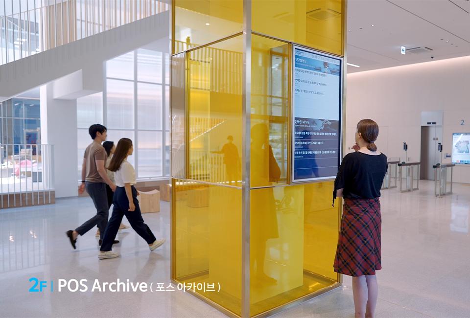 2F POS Archive(포스 아카이브)로 중앙에 위치한 노란 기둥에 붙은 모니터를 바라보고 있는 모습이다.