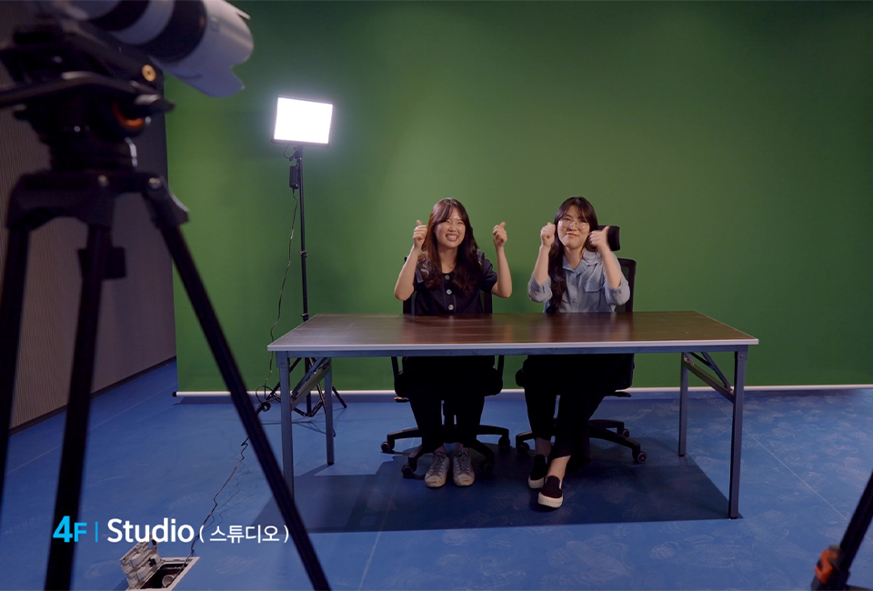 4F Studio (스튜디오) 공간에서 2명의 여자들이 양쪽 엄지를 들고 촬영을 하고 있는 모습.