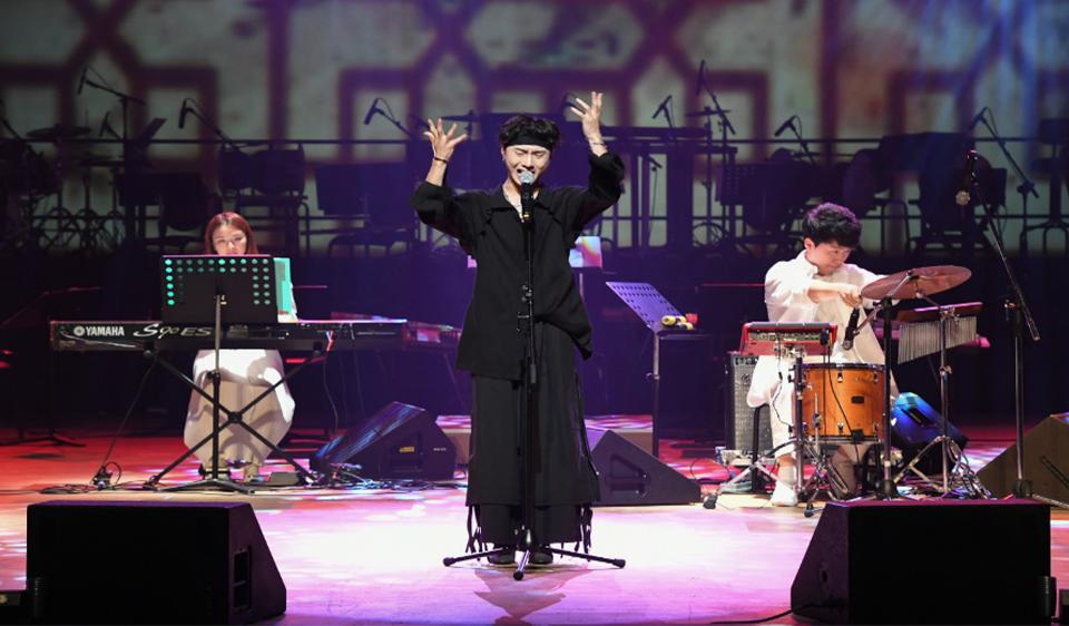 대학국악제 무대에서 공연을 하고 있는 모습. 가장 앞에 보컬, 좌측에 키보드, 우측에 드럼 연주자가 위치한다.
