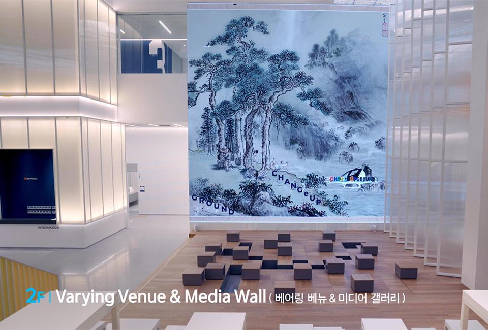 2F Varying Venue & Media Hall(베어링 베뉴와 미디어 홀) 의 모습. 미디어 아트 월이 뒷편의 벽 전면에 위치하며, 그 앞으로 의자들이 놓여 있는 모습이다.