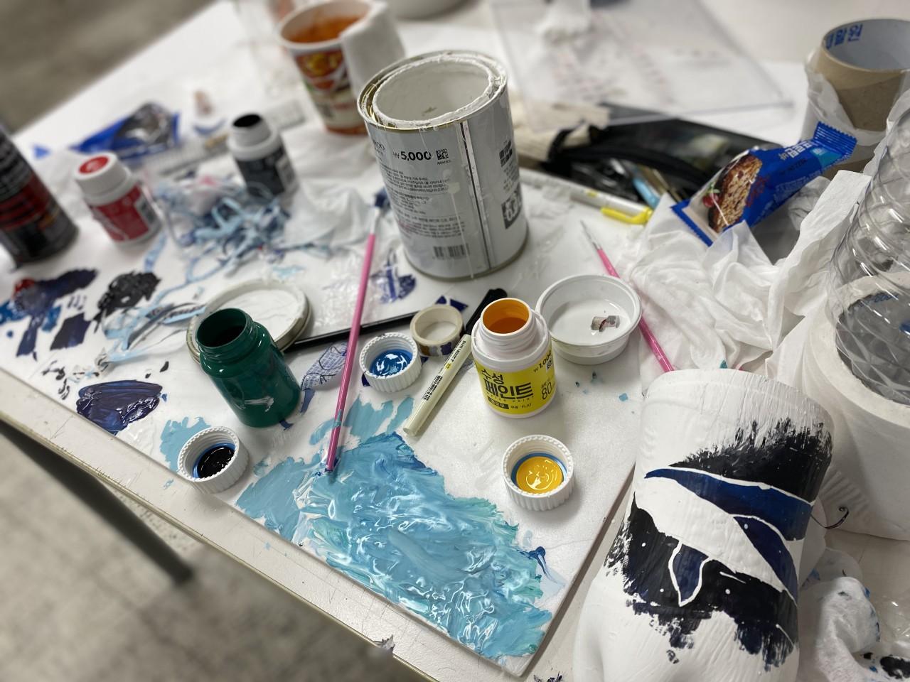 리사이클링 화분 제작을 위해 페인트 등의 미술도구로 작업을 진행하고 있는 작업 환경의 모습